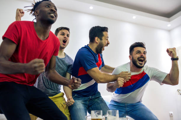 men watch a sports game friends sit in an apartment, watch a football match on television and cheer for their team man cave couch stock pictures, royalty-free photos & images
