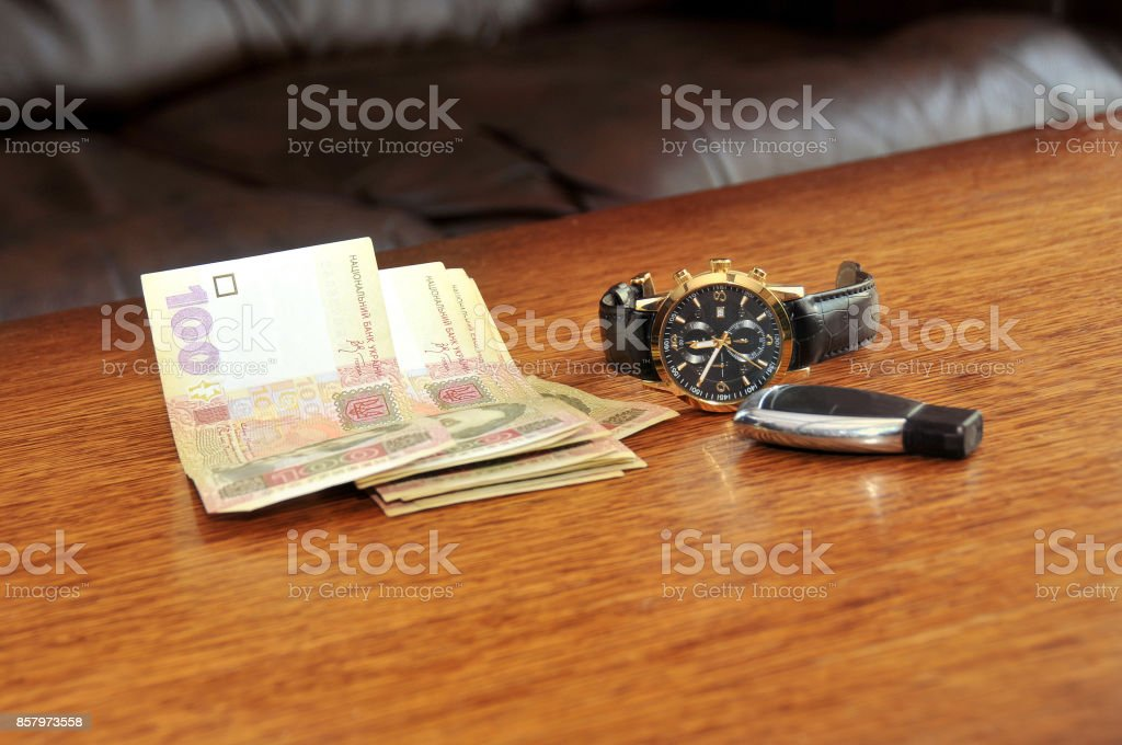 Men watch with a black leather wristband, ukraine money, car trinket on a wooden table stock photo