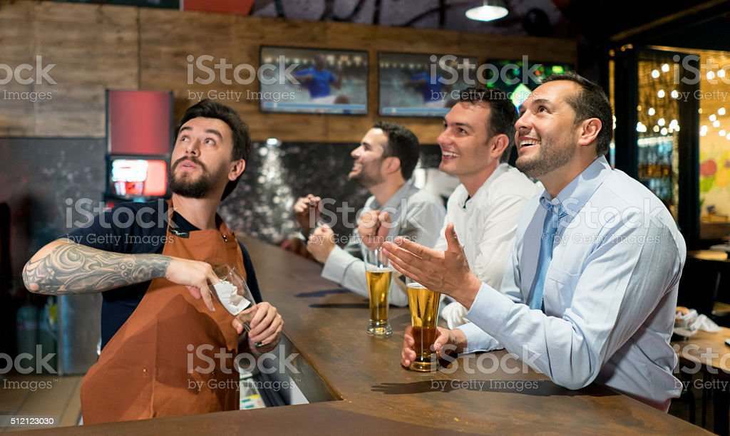 Men watching football at a sports bar - foto de acervo