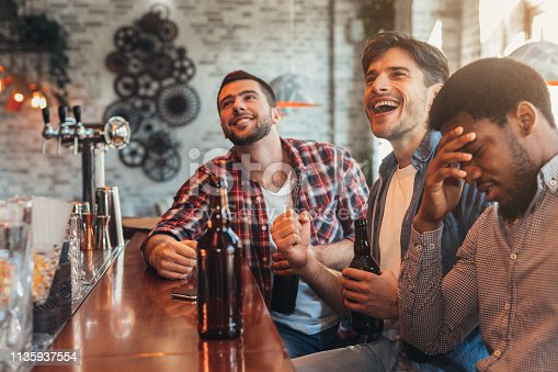 Men watching football match and drinking beer, in sport bar