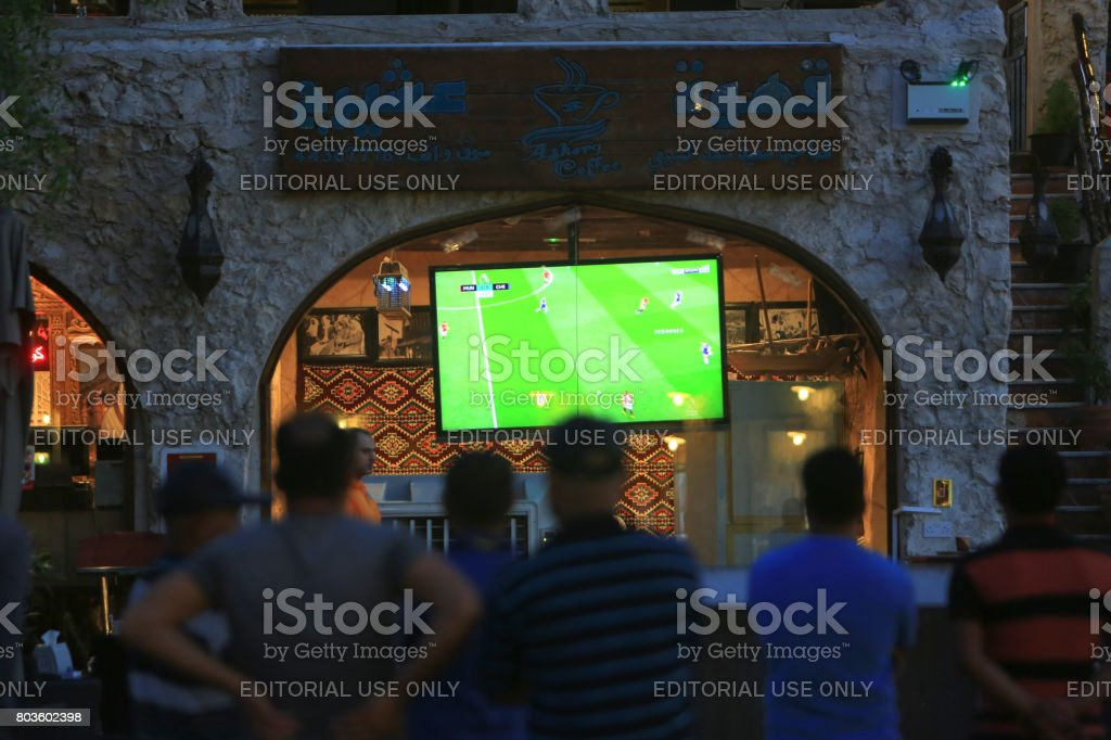 Men watching football on a TV in Souk Waqif, Doha, Qatar stock photo