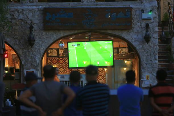 Men watching football on a TV in Souk Waqif, Doha, Qatar stock photo