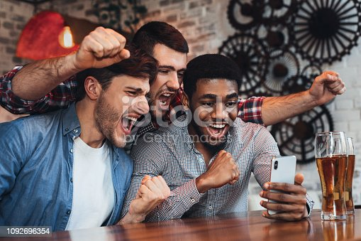 Men watching football on smartphone and drinking beer in bar