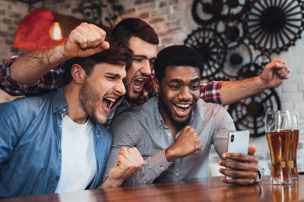 men watching football on smartphone in bar - adeptos imagens e fotografias de stock