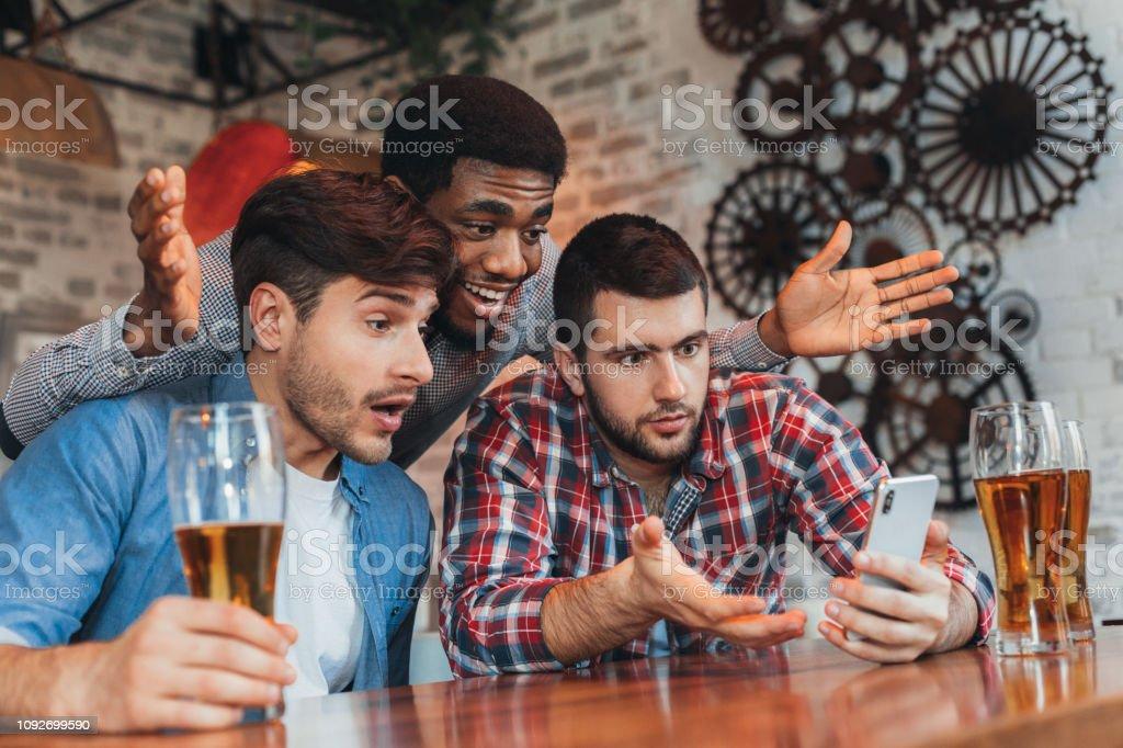 Hombres viendo resultados de partido de fútbol en smartphone - foto de stock