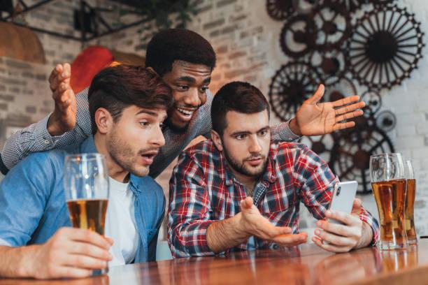 hombres viendo resultados de partido de fútbol en smartphone - solteros jóvenes fotografías e imágenes de stock