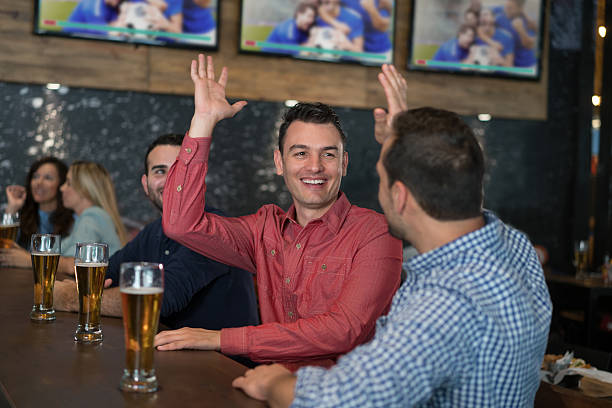 Men watching sports at the pub stock photo