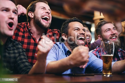 Men watching television and cheering for team