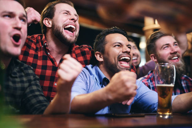 Men watching television and cheering for team Men watching television and cheering for team american football sport stock pictures, royalty-free photos & images