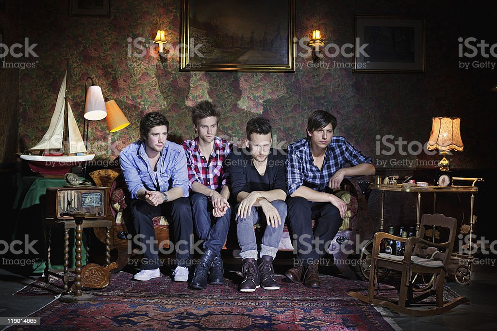 Men watching television in living room stock photo