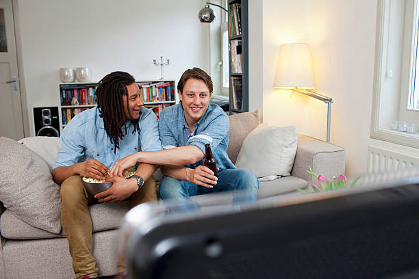 Men watching television in living room  man cave couch stock pictures, royalty-free photos & images