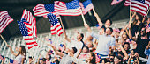 People standing and waving USA flags on a stadium during sport event.