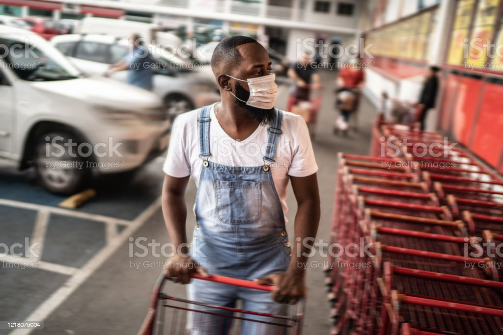 Men wearing face mask picking shopping cart in supermarket Men wearing face mask picking shopping cart in supermarket 30-34 Years Stock Photo