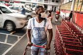 Men wearing face mask picking shopping cart in supermarket