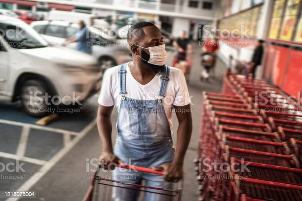 Men Wearing Face Mask Picking Shopping Cart In Supermarket Stock Photo - Download Image Now