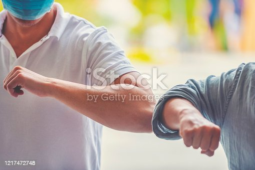 Men wearing surgical face masks practicing social distancing outdoors. They are doing an elbow bump greeting. Both are casually dressed.