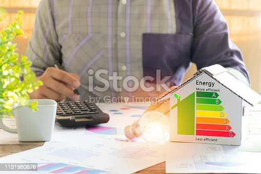 Men who are calculating cost savings from energy. Hand holding a pen. Detail of house efficiency rating on digital tablet screen. Concept of ecological and bio energetic house. Energy class.