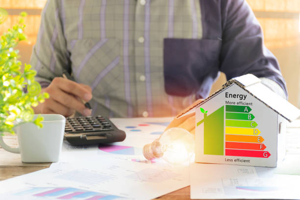 Men who are calculating cost savings from energy. Hand holding a pen. Men who are calculating cost savings from energy. Hand holding a pen. Detail of house efficiency rating on digital tablet screen. Concept of ecological and bio energetic house. Energy class. vitality stock pictures, royalty-free photos & images