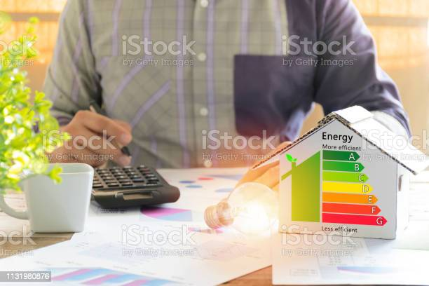 Photo of Men who are calculating cost savings from energy. Hand holding a pen.