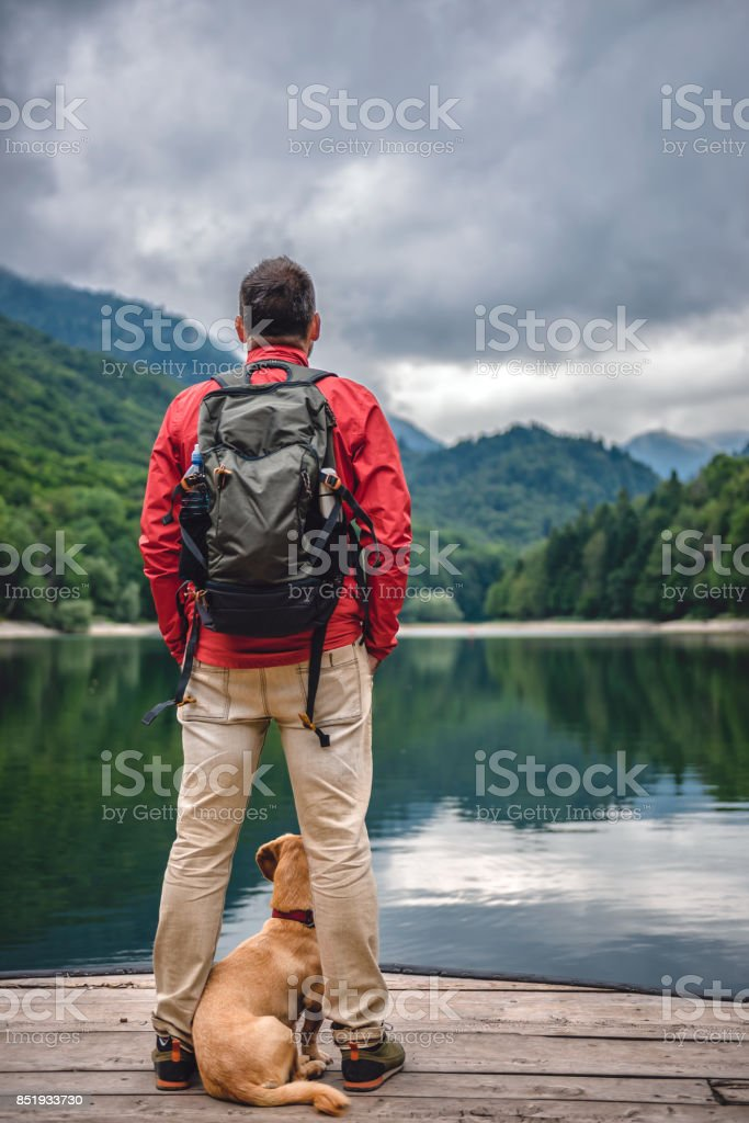 Men with a dog standing on pier by the lake stock photo