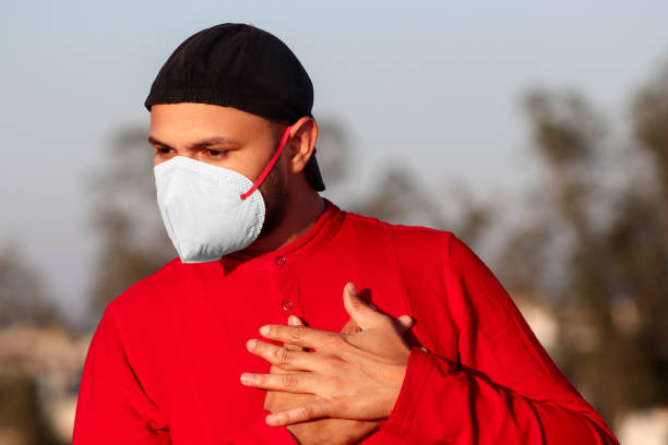 Men with chest pain, covering his face with pollution mask for protection against COVID-19 stock photo
