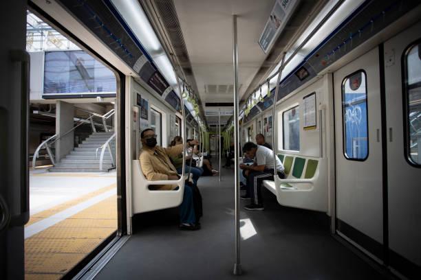 Männer mit Kinnbandmaske reiten im Zug – Foto