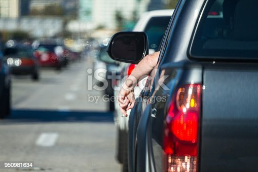 Men with cigarette out of the window smoking in traffic