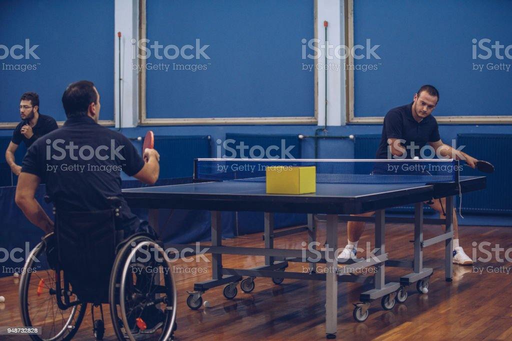 Men with differing abilities playing table tennis stock photo