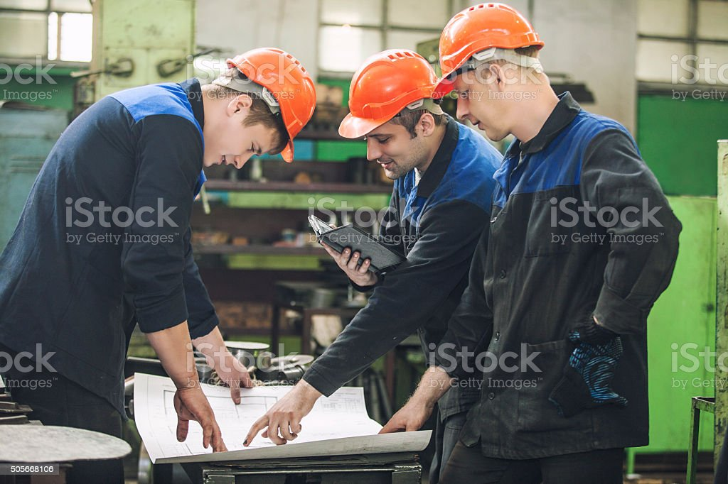 Men with drawings working in an old factory to install - Royalty-free Adult Stock Photo