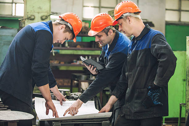 Men with drawings working in an old factory to install stock photo