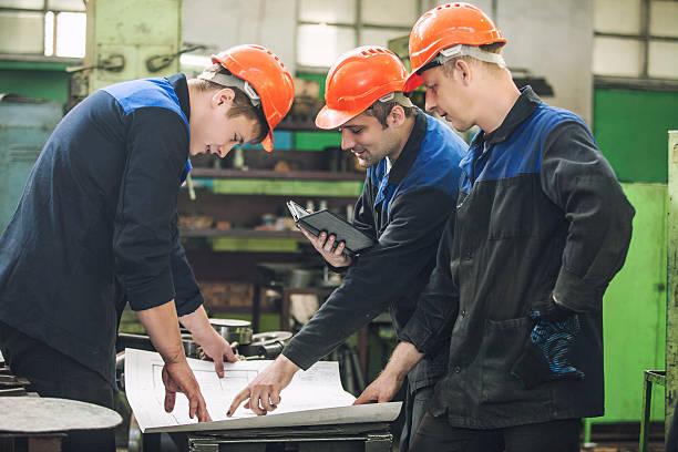 männer mit zeichnungen, die in eine alte fabrik zu installieren - kreativer speicher stock-fotos und bilder