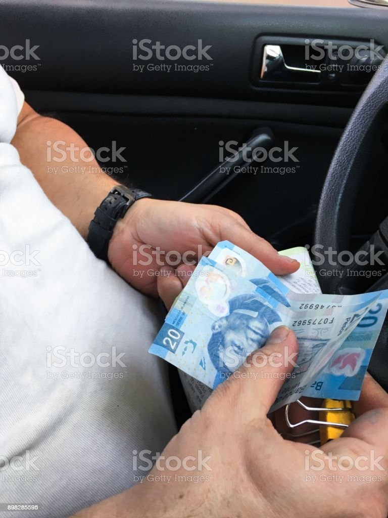A men with mexican pesos in the car stock photo