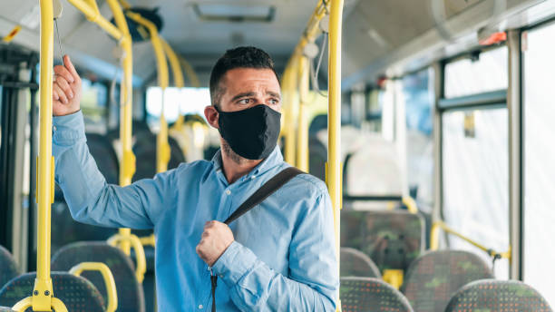 Men with protective face mask traveling with bus, during COVID-19