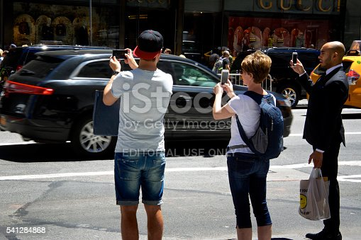 New York City, USA - June 14, 2016: A trio of people seen using their smartphones to take pictures or video of a political protest along 5th Avenue in Midtown, Manhattan.