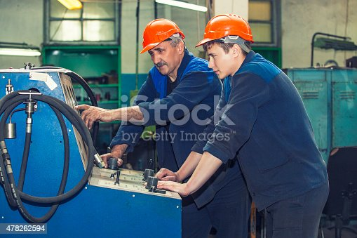 istock Men work on the old factory for the installation 478262594