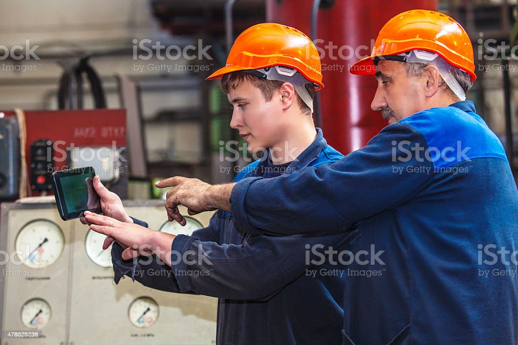 Men work on the old factory for the installation stock photo