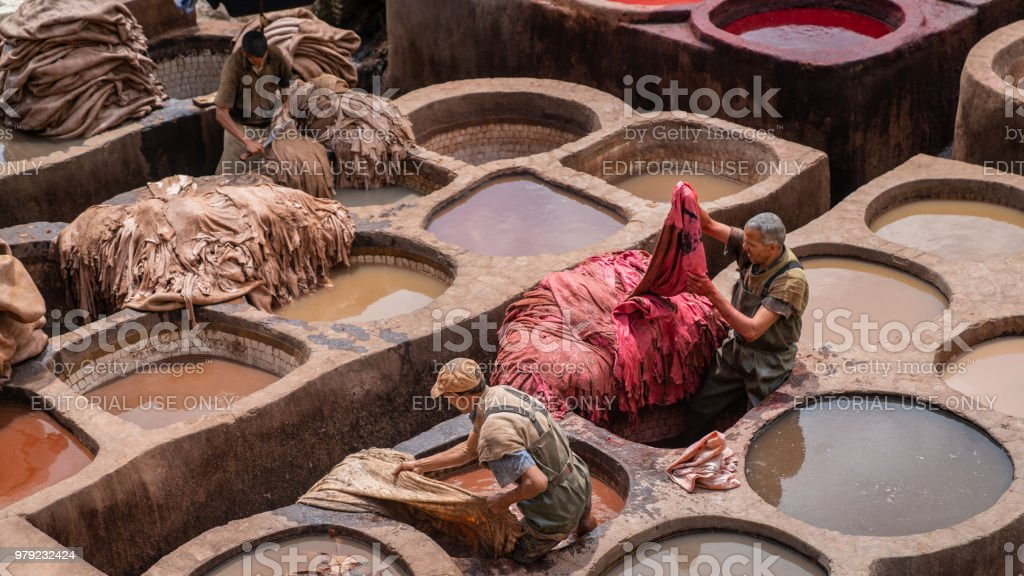 Men working as tanners in the dye pots at leather tanneries viewed...
