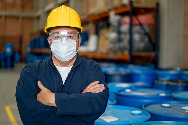 Men working at a chemical plant Man working at a chemical plant wearing protective wear drum container stock pictures, royalty-free photos & images