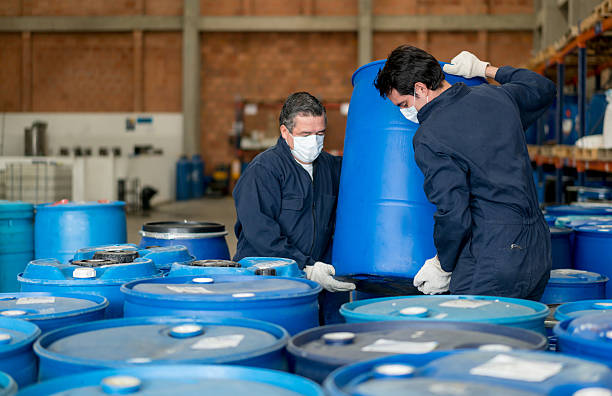 Men working at a chemical plant Men working at a chemical plant carrying barrels with toxic products chemical plant stock pictures, royalty-free photos & images