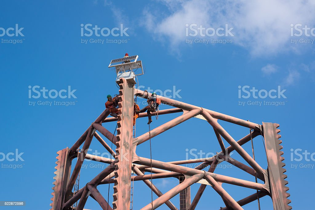 Men working at oil and gas rig leg Men working at top of oil rig leg for paintingMen working at top of oil and gas rig leg for painting Adult Stock Photo