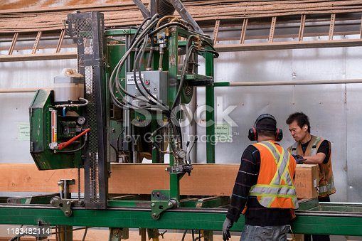 Two men working the industrial sawing machine. They are cutting a large piece of timber. They are wearing protective clothing.