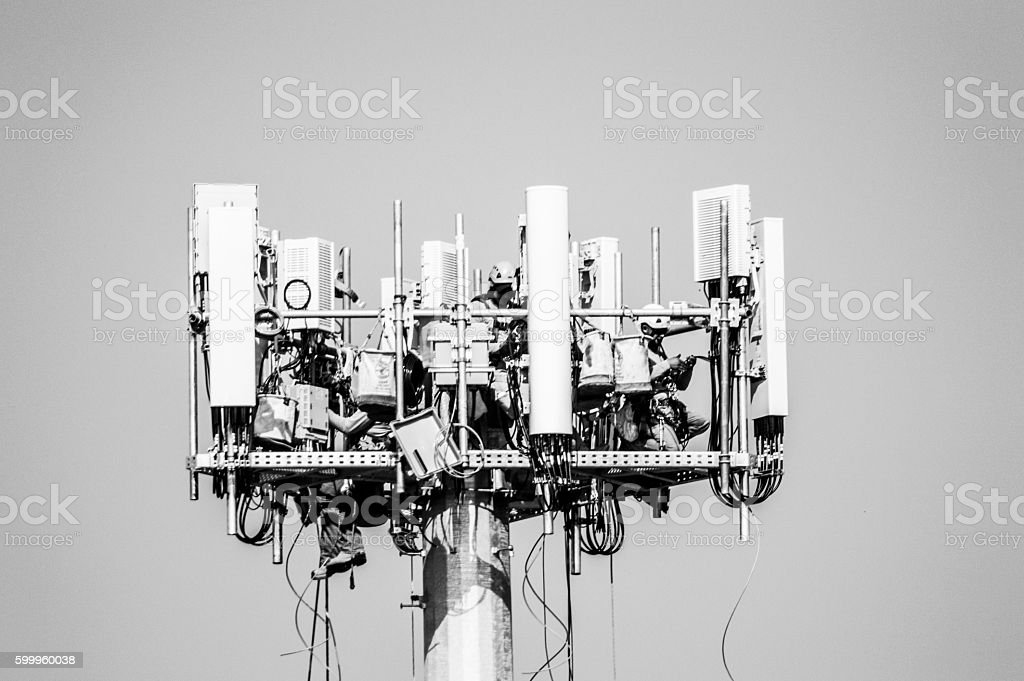 Men working on installing a cell phone tower stock photo