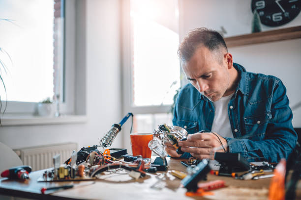 Men working with electronic components Men wearing blue denim shirt working with electronic components at his home office soldering iron stock pictures, royalty-free photos & images
