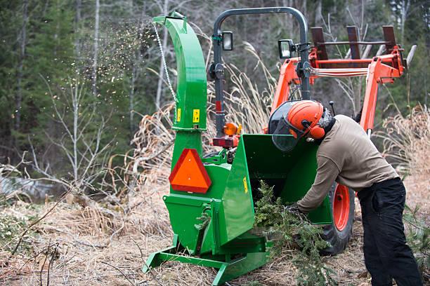 männer arbeiten mit häcksler und traktor - häcksler stock-fotos und bilder