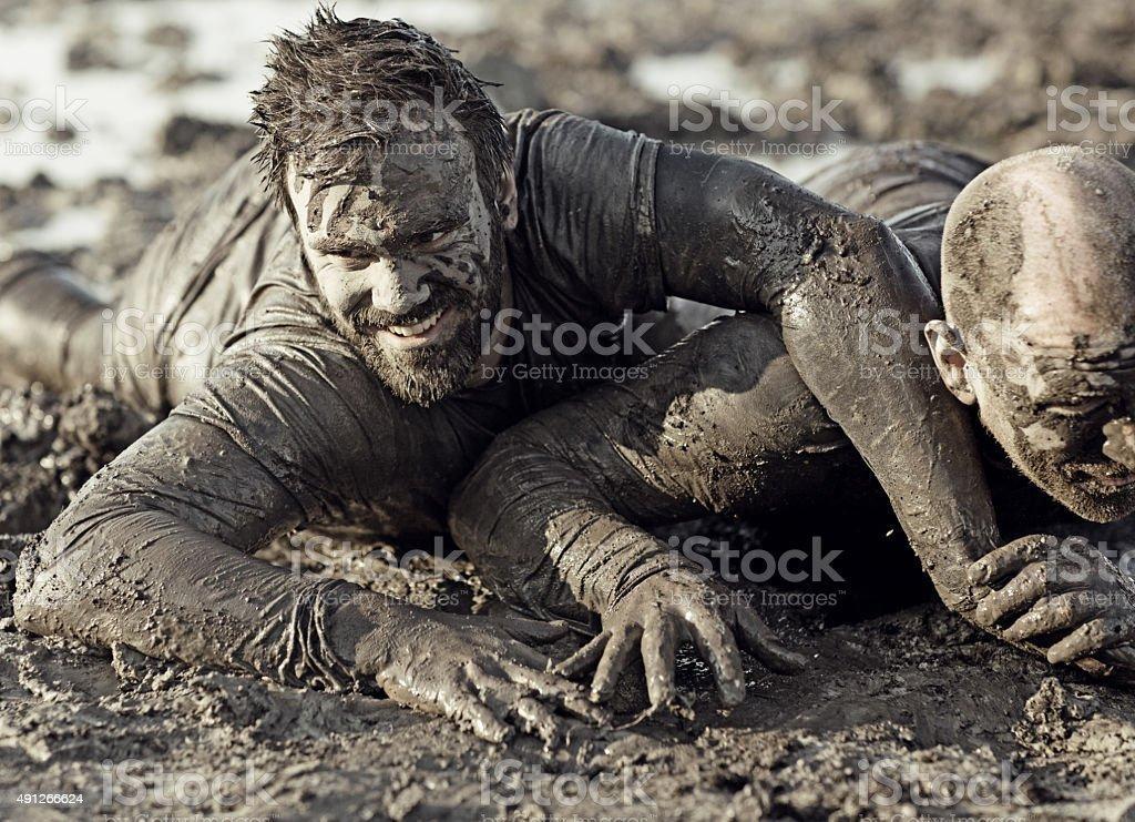 men wrestling in mud stock photo