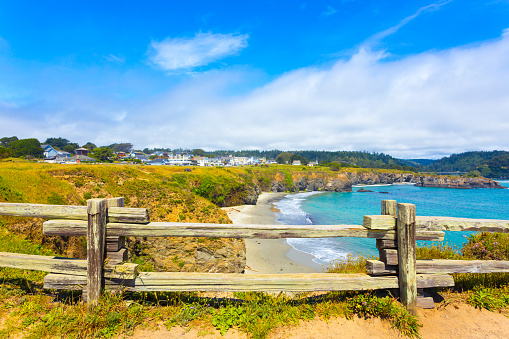 View through rustic wooden fence of sand beach below Main Street and houses of Mendocino town communinty on a sunny summer day in California. Horizontal