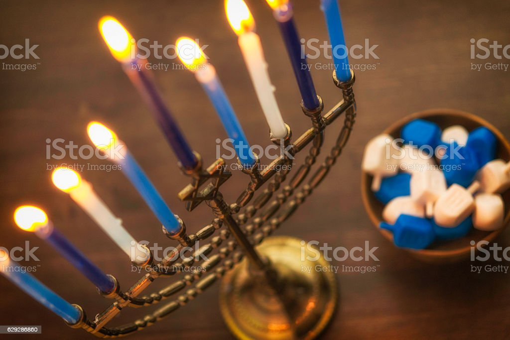Menorah with burning candles and dreidel. Hanukkah preparations stock photo