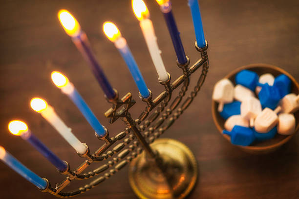 menorah with burning candles and dreidel. hanukkah preparations - chanukka stock-fotos und bilder