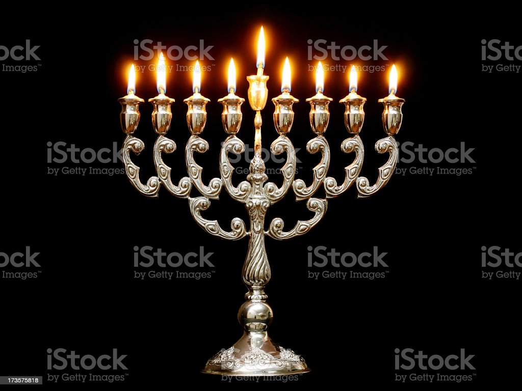 Menorah with nine lit candles on a black background stock photo