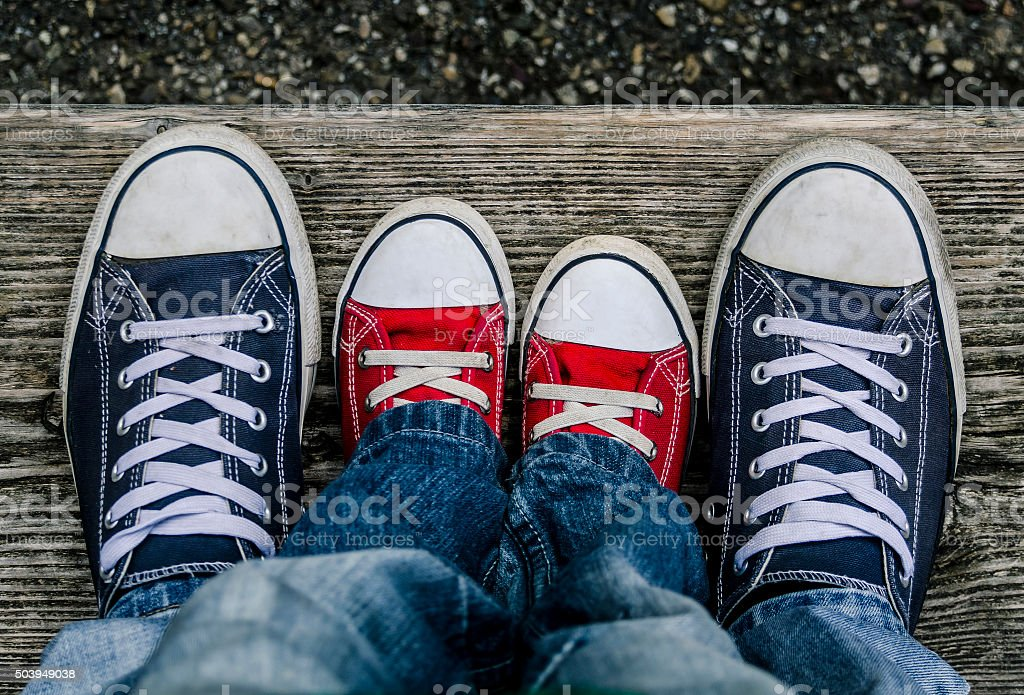 Men's and children's branded shoes together. stock photo
